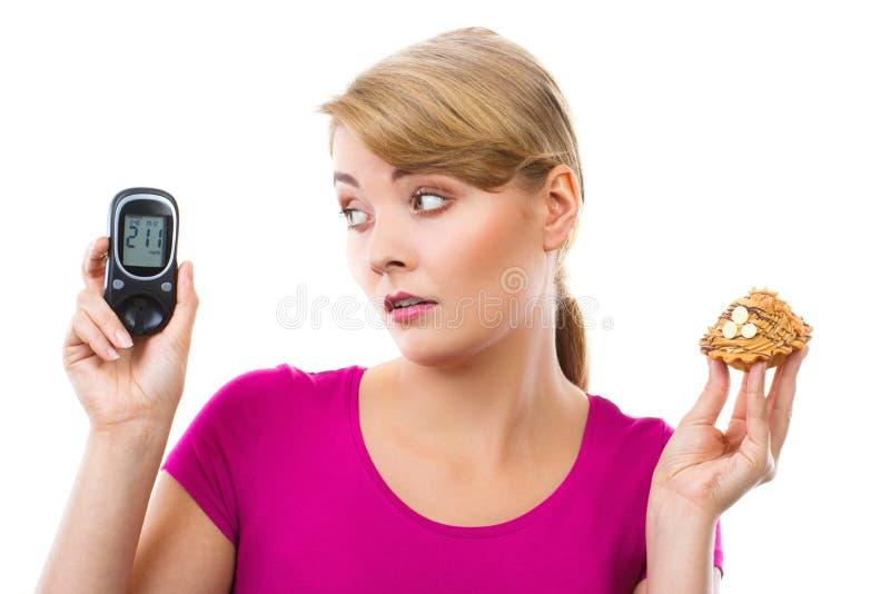 Szokujący kobiety mienia glucometer, świeża babeczka i, pojęcie cukrzyce obraz stock