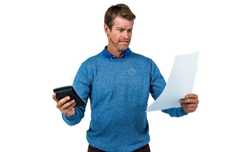 Szokujący mężczyzna mienia papier i kalkulator obrazy stock