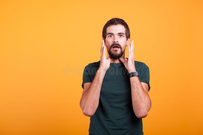 Szokujący mężczyzna patrzeje kamerę z rękami przy jego twarz obraz royalty free