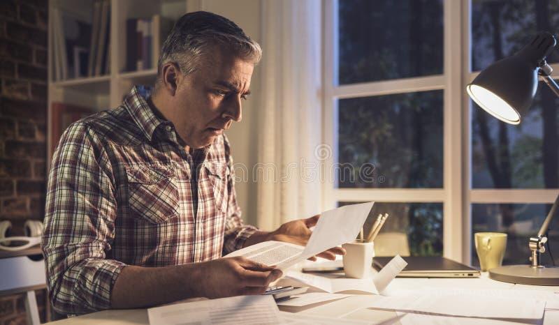Szokujący mężczyzna sprawdza rachunki w domu zdjęcie stock