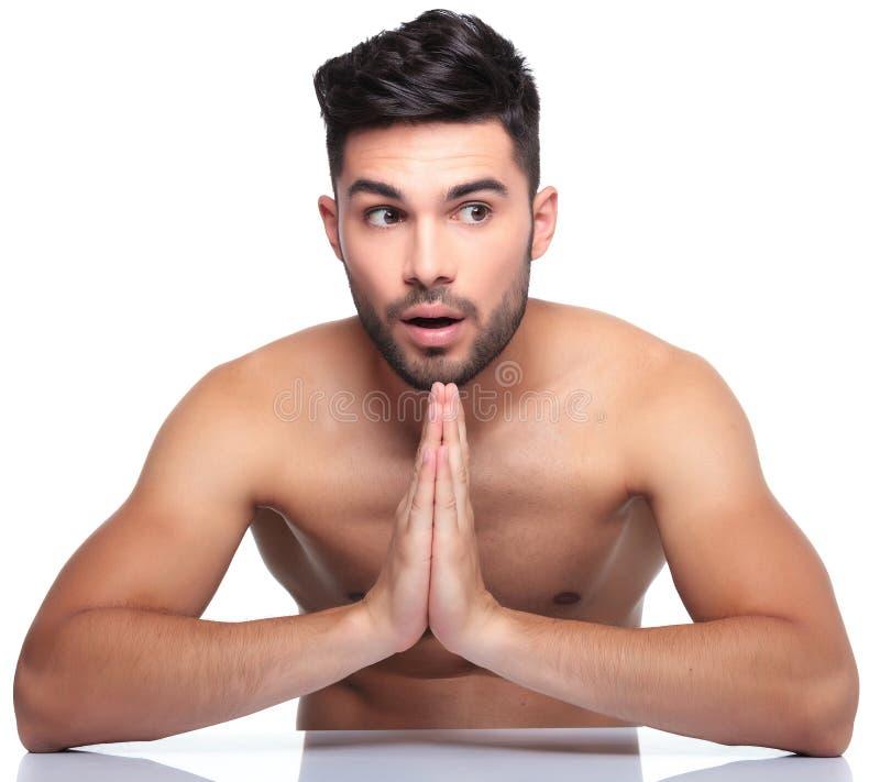 Szokujący młody człowiek ono modli się zdjęcie stock