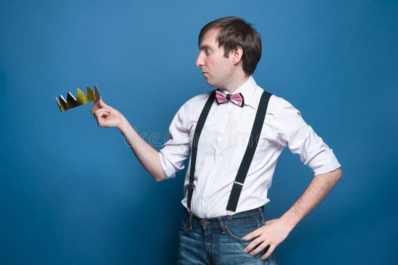 Szokujący przystojny mężczyzna w koszula, suspender, łęku krawacie z ręką na biodrze, mieniu i patrzeć złotą koronę, zdjęcia royalty free