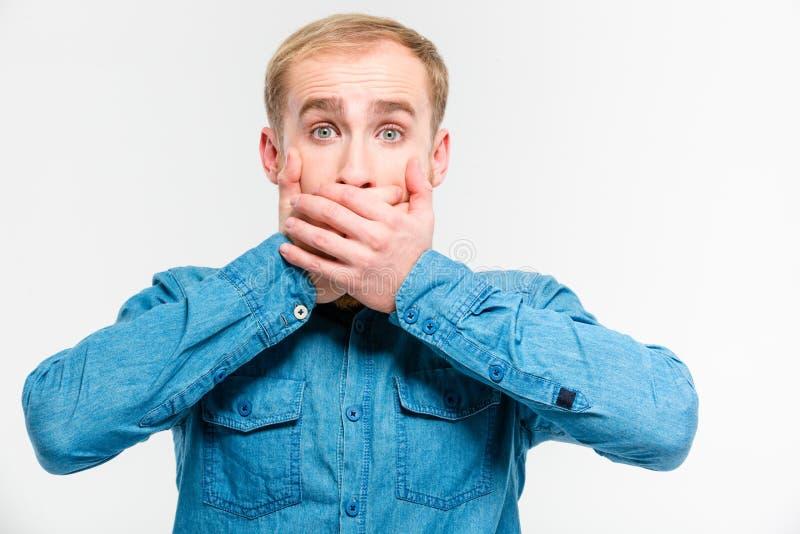 Szokuję oszałamiał mężczyzna zamykał jego usta rękami fotografia royalty free