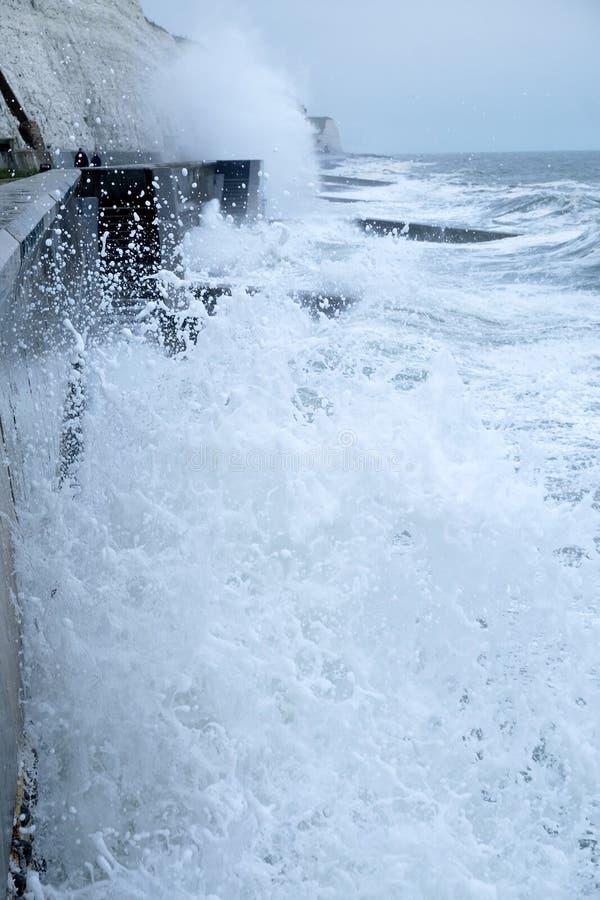 Szorstcy morza rozbija przeciw Brighton dennej ścianie z falezami behind fotografia stock