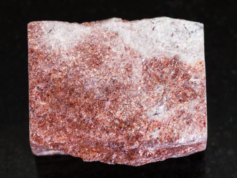 szorstki różowy awanturynu kamień na ciemnym tle obraz stock