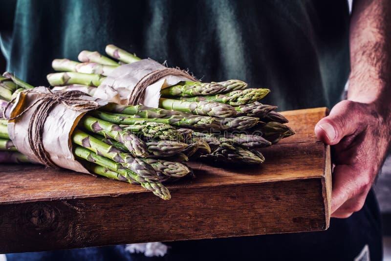 szparagi asparagus surowy szparagi świeże Zielony asparagus Wiązany asparagus w inny pozycje Rolnik niesie wiązanego asparagus zdjęcie royalty free