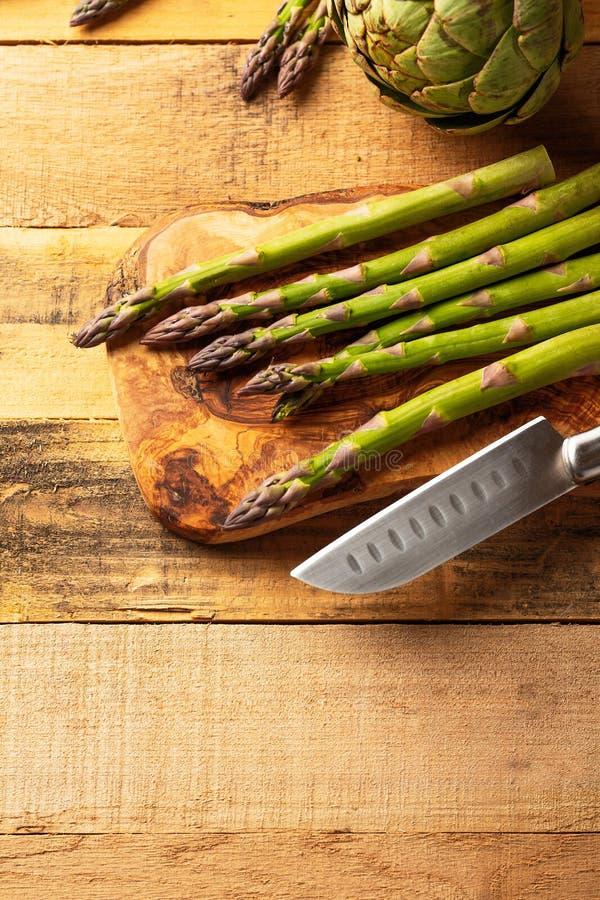 szparagi i karczoch na tnącej desce z nożem, pokrajać Na drewnianym tle t?o kulinarny dieta deliciouses zdjęcia stock