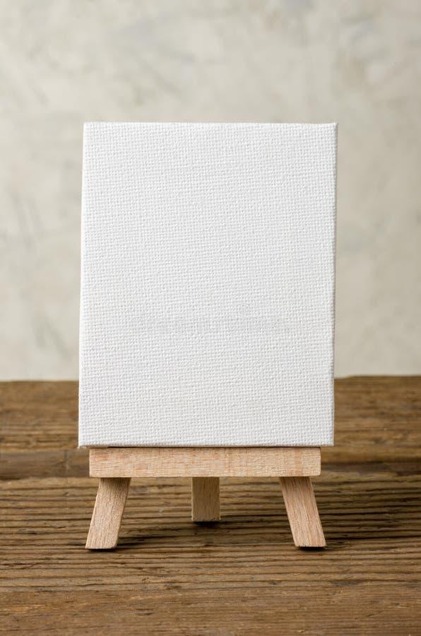 Sztaluga z pustą kanwą na drewnianym tle obrazy stock
