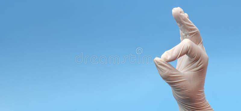 sztandar Czerep ręka która pokazuje OK gest na błękitnym tle w medycznych lateksowych białych rękawiczkach mapy t?a oko medical o obrazy stock