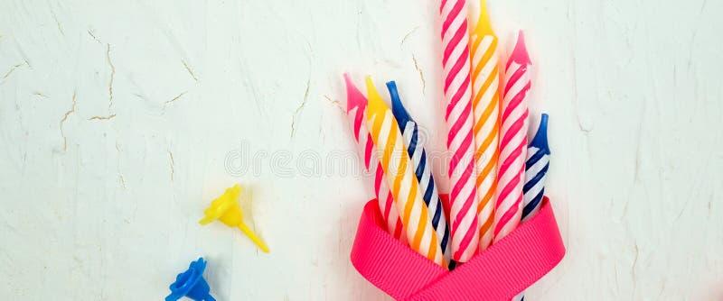 sztandar dla strony internetowej, pasiaste kolorowe świeczki z różowym faborkiem dla przyjęcia urodzinowego na białym tle Mieszka zdjęcie royalty free