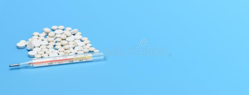sztandar Medyczny rtęć termometr pokazuje wysoką ciało temperaturę i udziały round białe pigułki na błękitnym tle painkiller zdjęcia stock