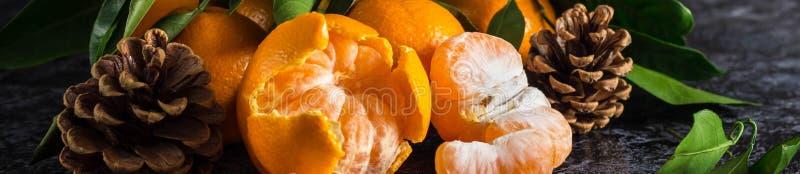 Sztandar pomarańczowi tangerines z zielenią opuszcza na ciemnym tle Obrani mandarynka plasterki, ro?ki i zdjęcia royalty free