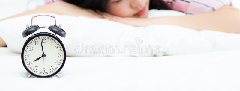 Sztandar strony internetowej zbliżenia budzik i piękna azjatykcia młoda kobieta w ranku, budzimy się dla sen z budzikiem, relaksu zdjęcie stock