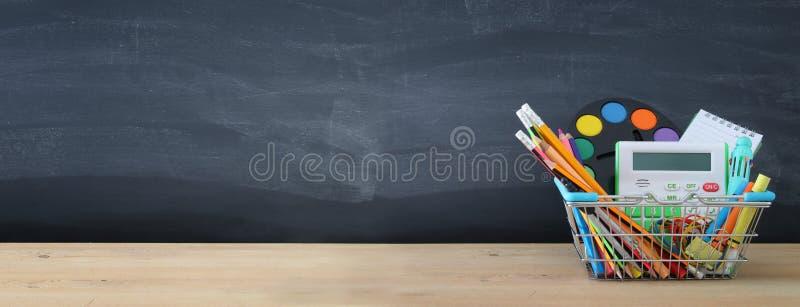 Sztandar wózek na zakupy z szkolną dostawą przed blackboard tylna koncepcji do szkoły zdjęcie stock