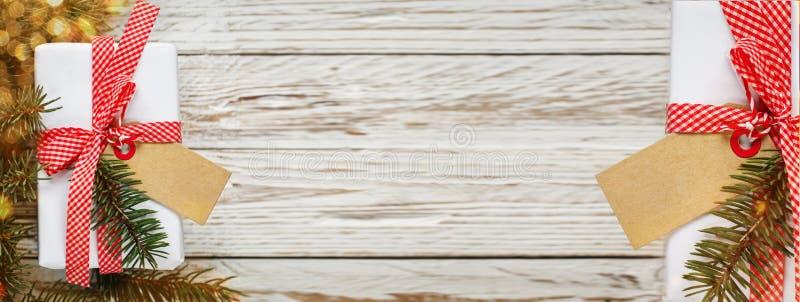 sztandar Wakacyjnego prezenta pudełko Bożenarodzeniowa teraźniejszość z etykietką przy białym drewnianym stołem Projekt kopii prz zdjęcia stock