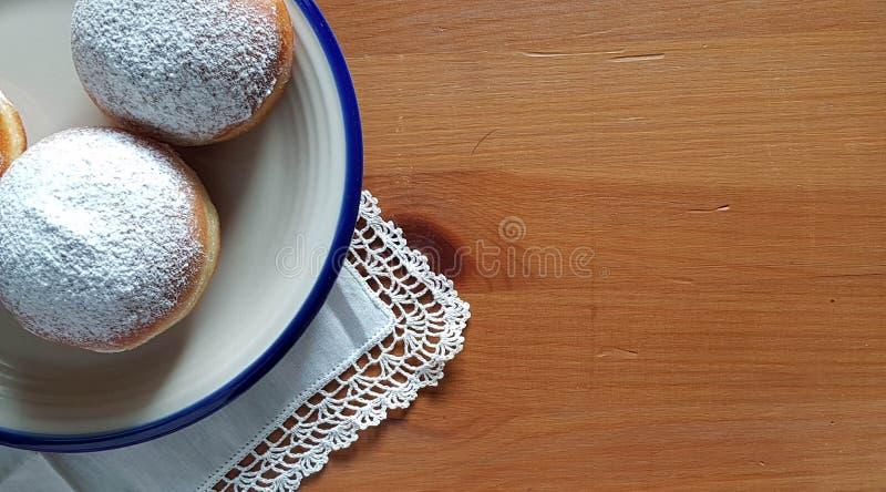 Sztandar - Zasięrzutny widok donuts kłama na ceramicznym talerzu na nieociosanym drewnianym stole Udział kopii przestrzeń zdjęcie stock