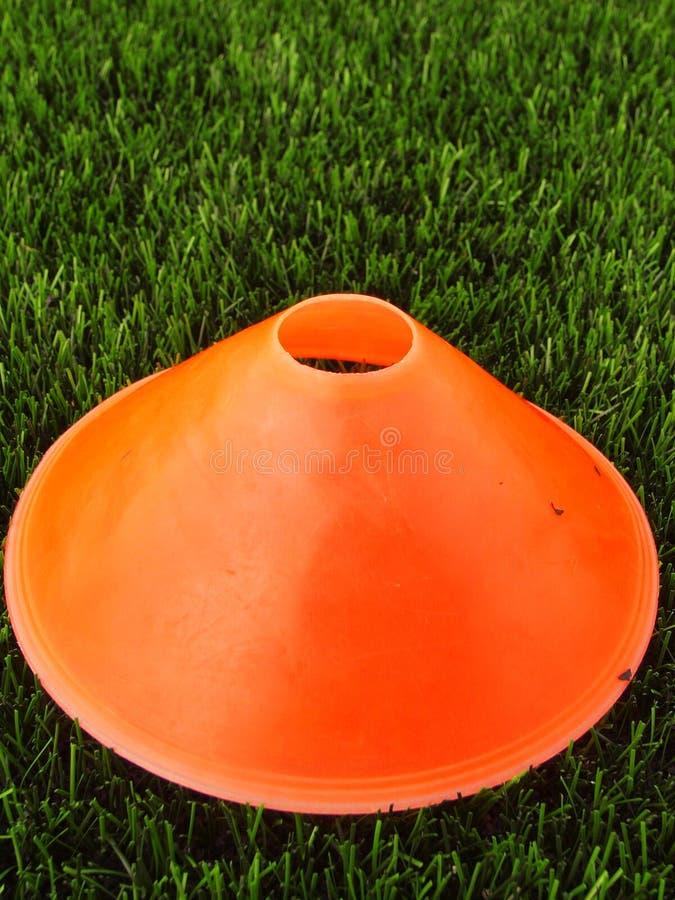 Sztuczna zielona plastikowa trawa w tle z jaskrawym pomarańczowym klingerytu rożkiem Mark na zimy footbal boisku obrazy stock