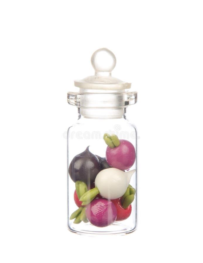 Sztuczni warzywa w butelce odizolowywającej na bielu obrazy stock