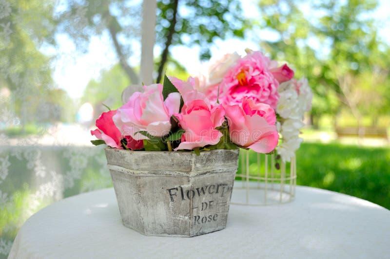 Sztuczny różany bukiet w drewnianej wazie zdjęcia stock