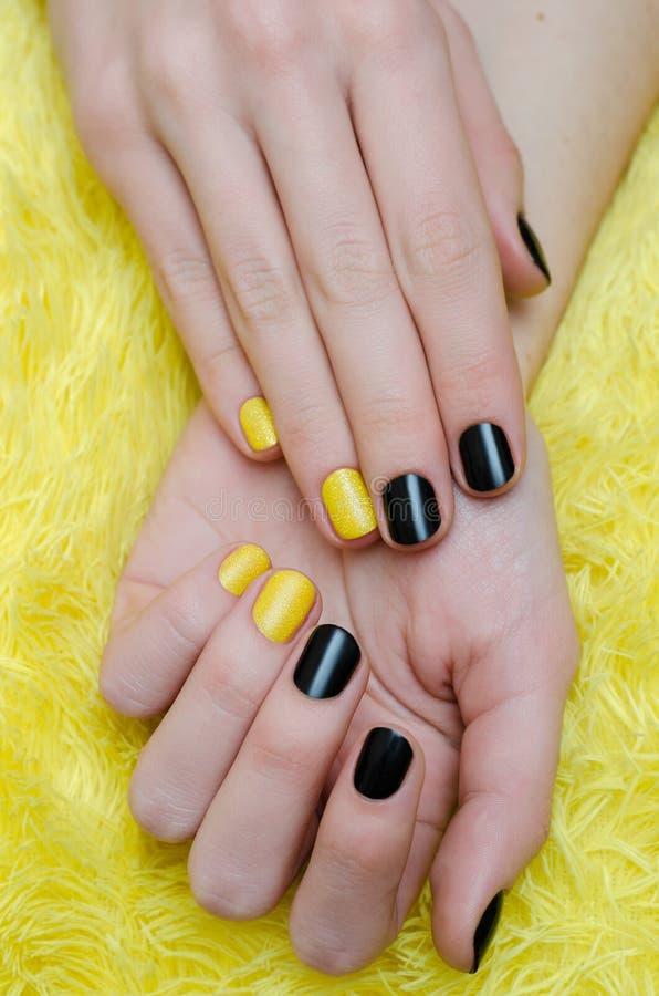 sztuka gwóźdź Piękna żeńska ręka z czernią i żółtym manicure'em zdjęcie stock