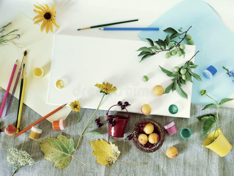 Sztuka materiały, farby, muśnięcia, barwioni ołówki, biała kanwa, kwiaty i owoc na lekkim tle, odgórny widok, pojęcie summ obrazy royalty free