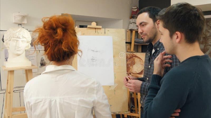 Sztuka nauczyciel wyjaśnia dwa męskich uczni dlaczego rysować tynk obsadę fotografia stock