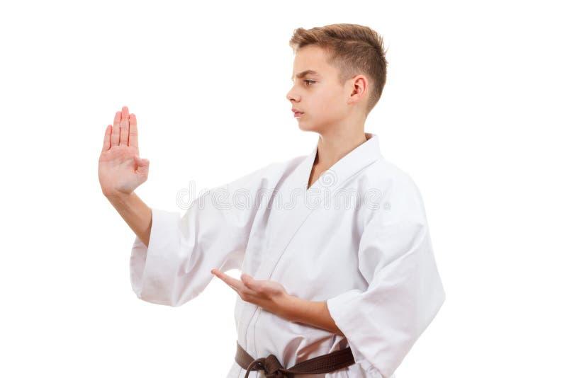Sztuka samoobrony sporta karate - dziecko nastoletnia chłopiec w białym kimonowym szkolenie bloku i ponczu obraz royalty free