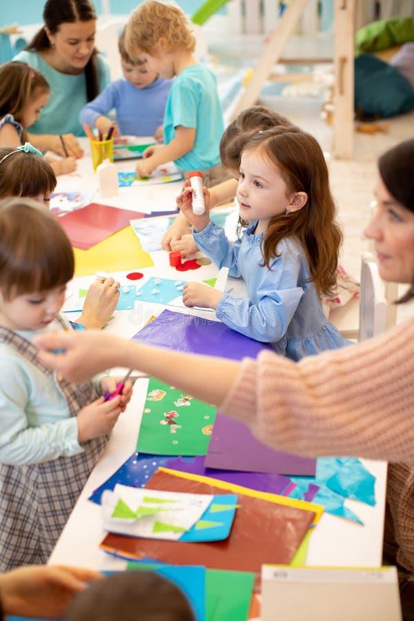 Sztuki i rzemiosła aktywność w dziecinu Grupa preschool dzieciaki wręcza działanie w opieki dziennej centrum obraz stock