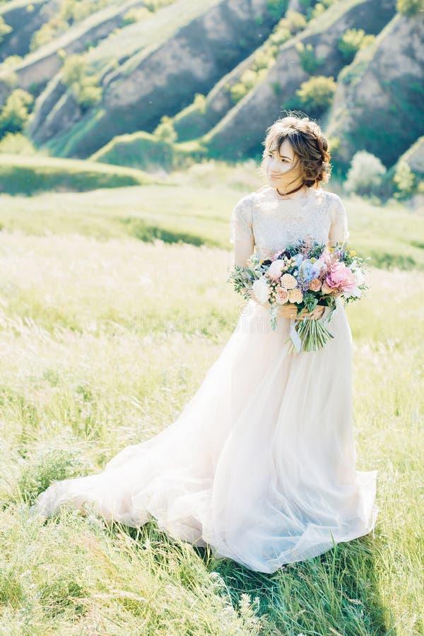 Sztuki piękna ślubna fotografia Piękna panna młoda z bukietem i suknia z pociągiem w naturze fotografia royalty free