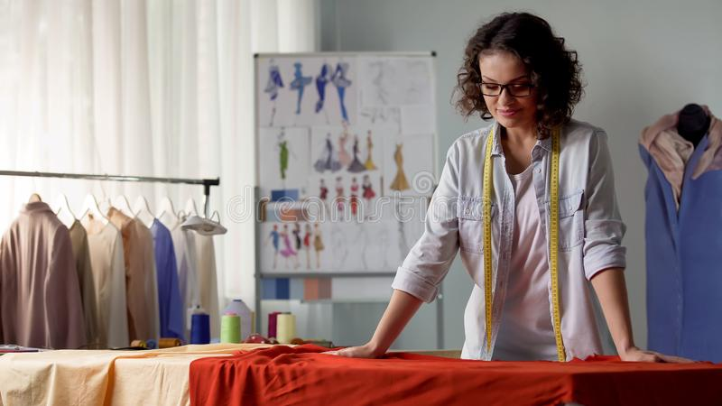 Szwaczka patrzeje atłasową czerwoną tkaninę, tworzy nową mody kolekcję, atelier zdjęcia royalty free