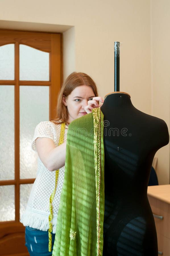 Szwaczka stoi blisko drzwiowego i pomiarowego zielonego płótna na mannequin zdjęcia royalty free