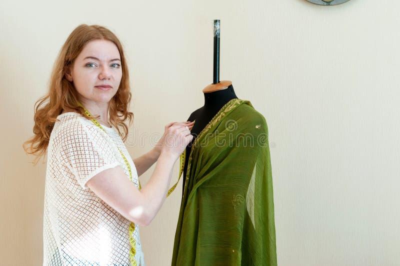 Szwaczka stoi blisko mannequin, wieszający w górę sukiennej i patrzeje kamery obrazy royalty free