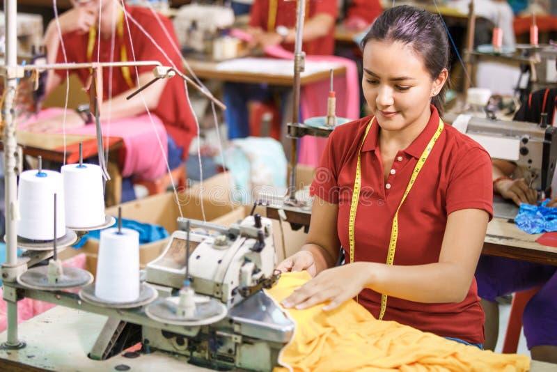 Szwaczka w tekstylny fabryczny szyć z przemysłowym szwalnym machem zdjęcia stock
