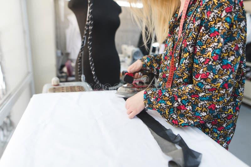 Szwaczki dziewczyna odprasowywał płótno z żelazem szew pracy z płótnem Klejenie tkanina tła guzików zbliżenia pojęcia ciemna igie obrazy stock
