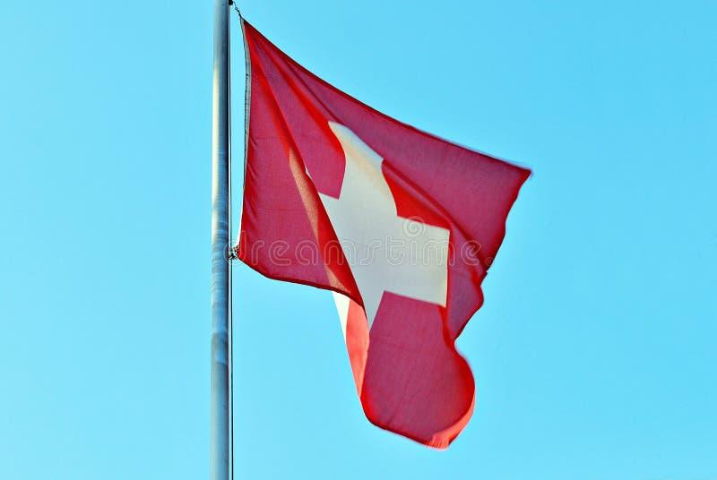 Szwajcar flaga przeciw niebieskiemu niebu zdjęcia royalty free