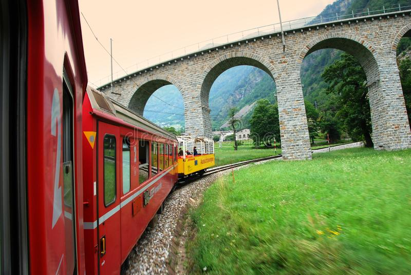 Szwajcaria: Lipiec 2012, Sławny czerwony wysokogórski taborowy Bernina Ekspresowy od StMoritz Tirano blisko Brusio wiaduktu w Wło obrazy stock