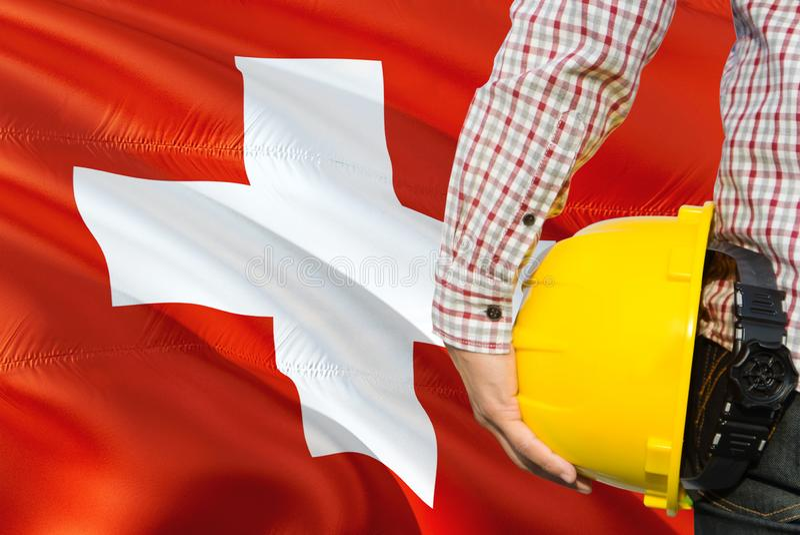 Szwajcary Konstruują trzymają żółtego zbawczego hełm z machać Szwajcaria chorągwianego tło Budowy i budynku poj?cie fotografia stock