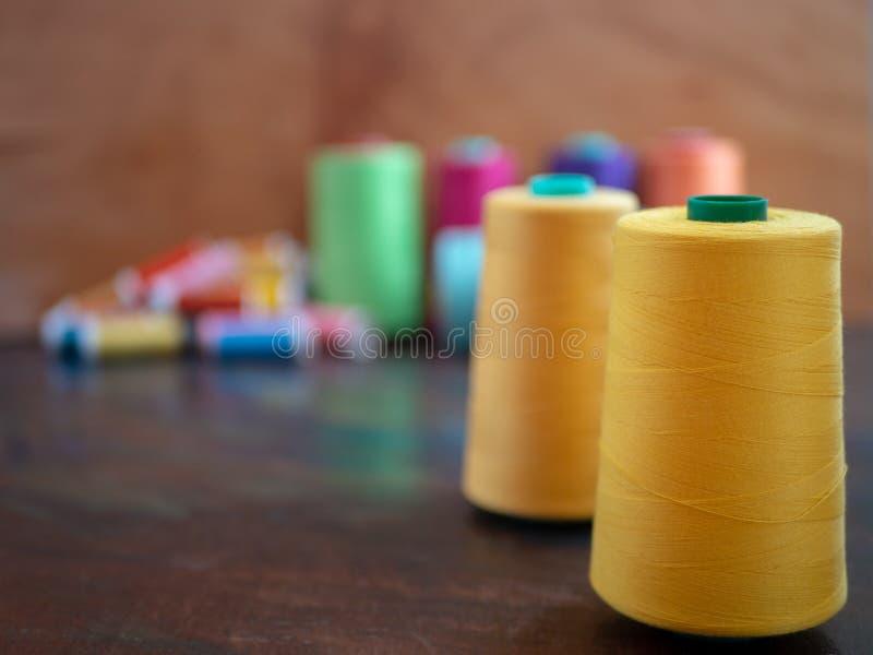 Szwalne nici w wiele kolorach na zmroku stole z dużymi rożkami w kolorze żółtym zdjęcie stock