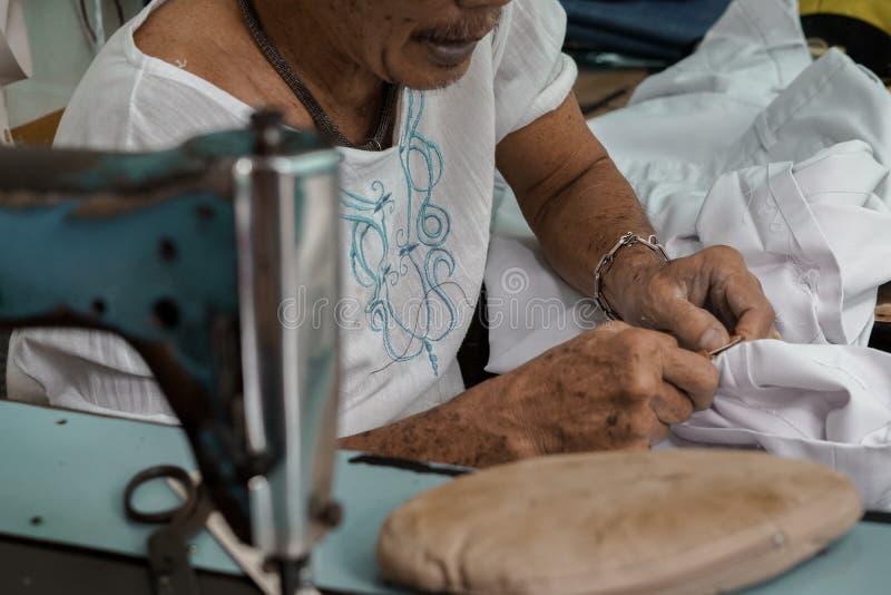 Szwalnej maszyny i miejscowego krawczyna pracuje w tkaninie, szy tkaninę Ten ` s strzał nabierał Tajlandia zdjęcia stock