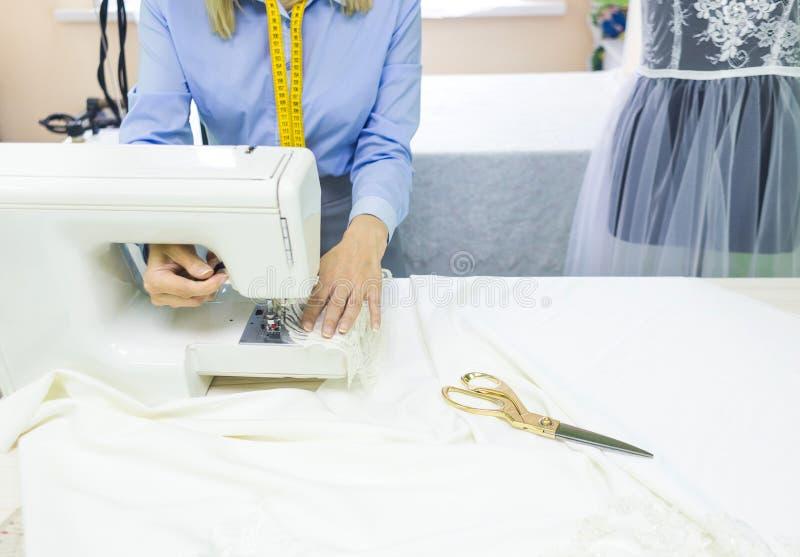 Szwalny warsztat ręki target3574_1_ miarę szwaczki pracy Młoda kobieta pracuje z szwalną maszyną zdjęcia royalty free
