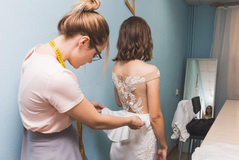 Szwalny warsztat ręki target3574_1_ miarę szwaczki pracy Szwaczka bierze pomiary ślubna suknia fotografia royalty free