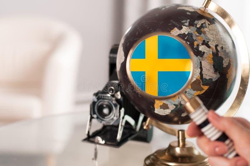 Szwedzi flaga na kuli ziemskiej pod powiększać obrazy stock