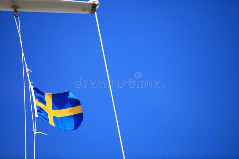 Szwedzi flaga na statku niebieskim niebie na tle obrazy royalty free