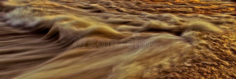 Szybka bieżąca woda w długim ujawnieniu dla tła i okładkowej fotografii - złota brąz zdjęcia stock