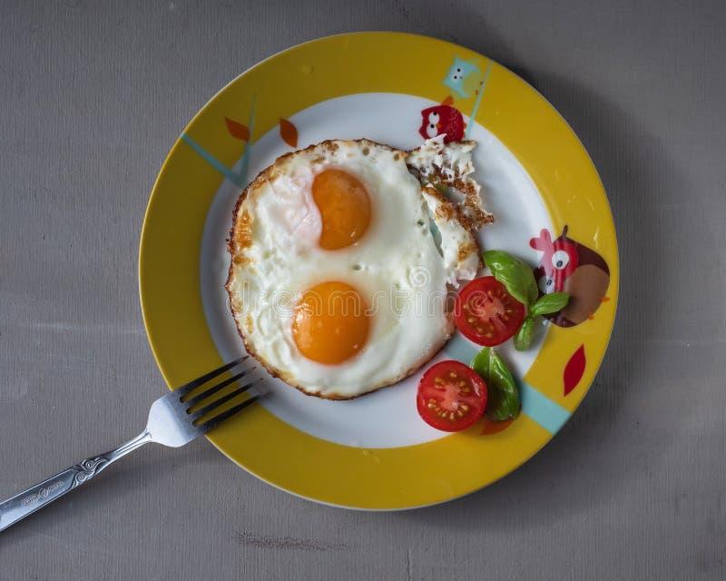Szybki śniadanie dwa jajka, rozdrapani jajka, pomidory zdjęcie stock