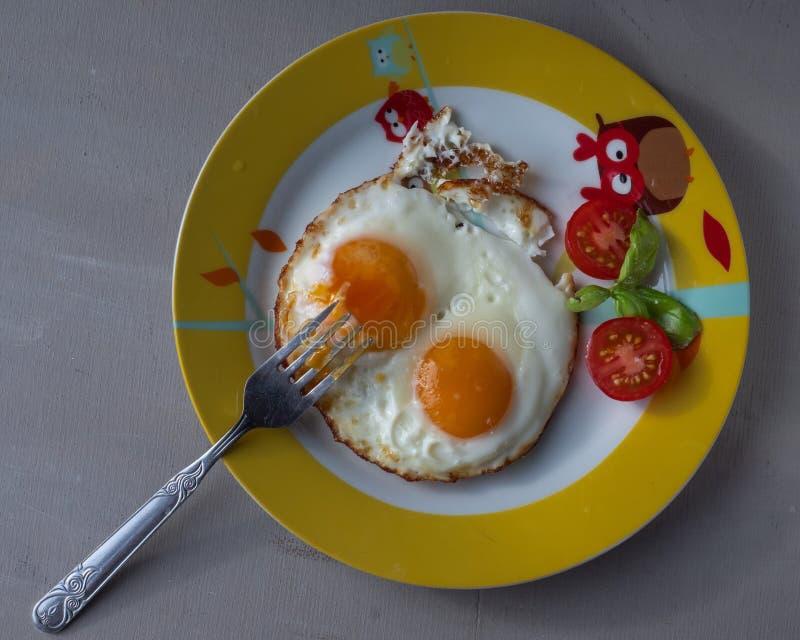 Szybki śniadanie dwa jajka, rozdrapani jajka z pomidorami na round talerzu na szarym tle, strzał od odgórnego kąta fotografia royalty free
