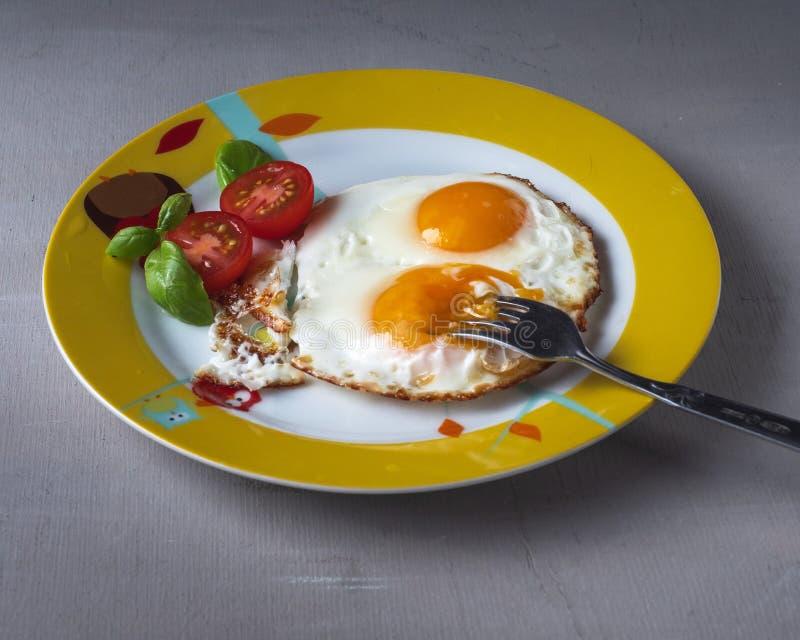 Szybki śniadanie dwa jajka z pomidorami na round talerzu z rozwidleniem na szarym tle, boczny widok zdjęcie stock