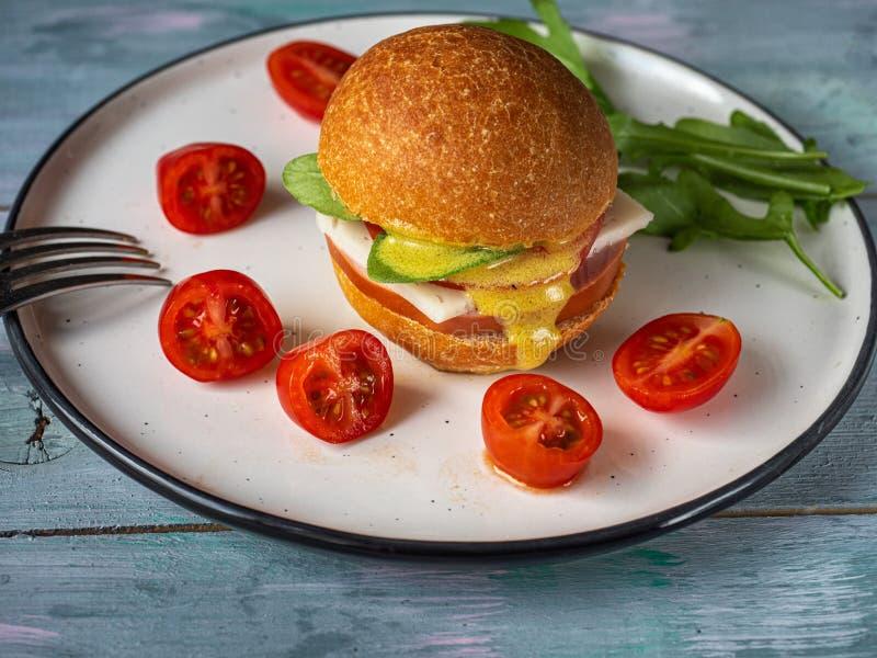 Szybki lunch hamburger i czereśniowy pomidor na jaskrawym ceramicznym talerzu obraz stock