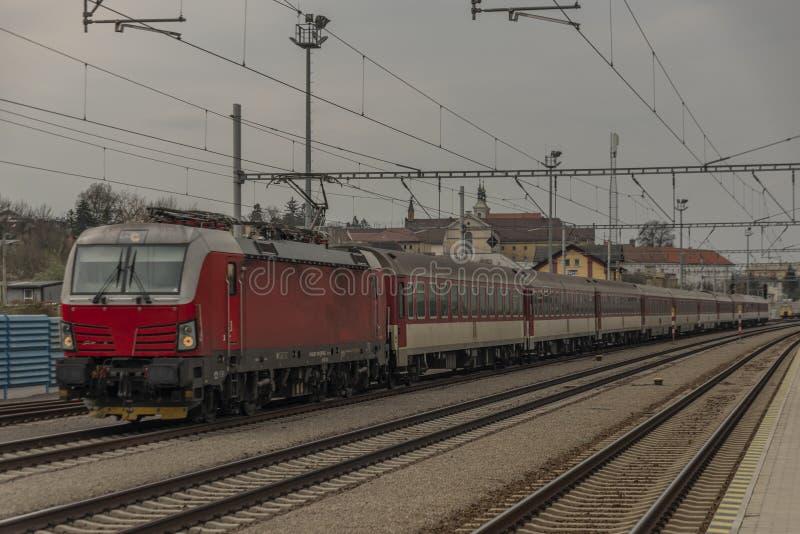 Szybki pociąg pasażerski z czerwonym nowoczesnym silnikiem elektrycznym na stacji Ilava fotografia royalty free