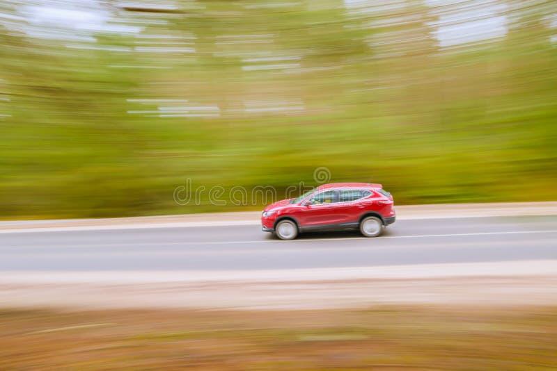 Szybki poruszający czerwony samochód na asfaltowej drodze Panning strzał, zamazany bac fotografia royalty free